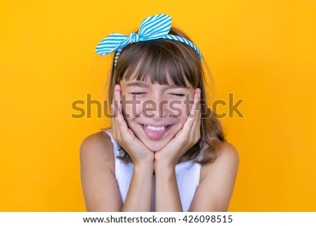 Expressing joy! Happy pretty girl in white dress. Yellow background. - stock photo