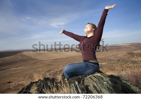 Expressing  woman  Sits on the stone and Arms Raised to heaven. - stock photo