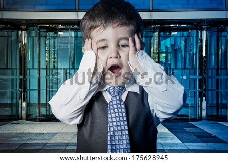 Expression, child dressed businessman with hands in his tie and skyscrapers in the background - stock photo