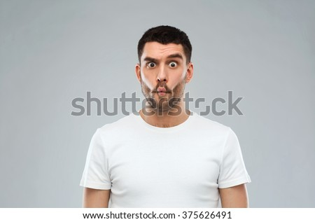 expression, fun and people concept - man with funny fish-face over gray background - stock photo