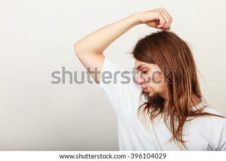 Expression of very bad smell. Young long haired sweaty man making hand gesture. Sweating concept. - stock photo