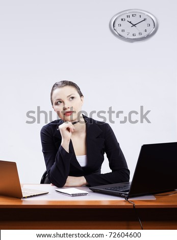 expression office portrait of beautiful young thougthful business woman sitting at her workplace with two laptops on gray
