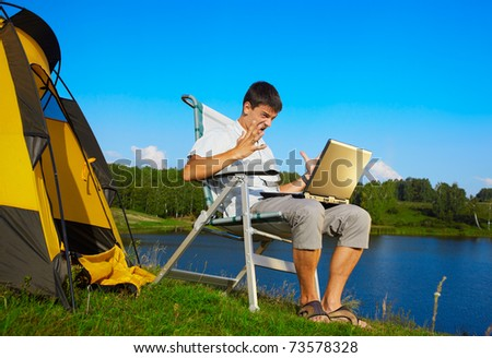 expression portrait of angry man with laptop sitting in folding chair near camp tent outdoors - stock photo