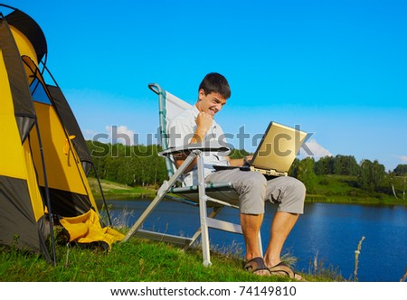 expression portrait of succesful man with laptop sitting in folding chair near camp tent outdoors - stock photo