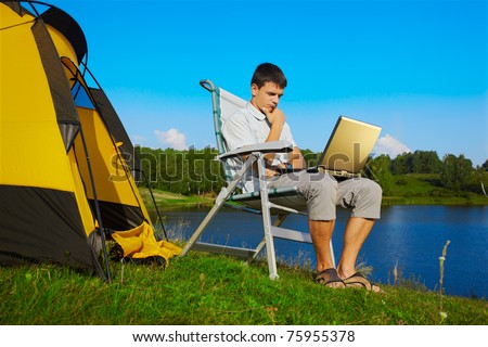 expression portrait of thoughtful man with laptop sitting in folding chair near camp tent outdoors - stock photo