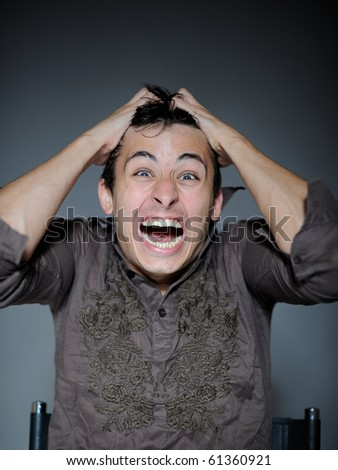 Expressions. Handsome young man feeling fear and pain - stock photo