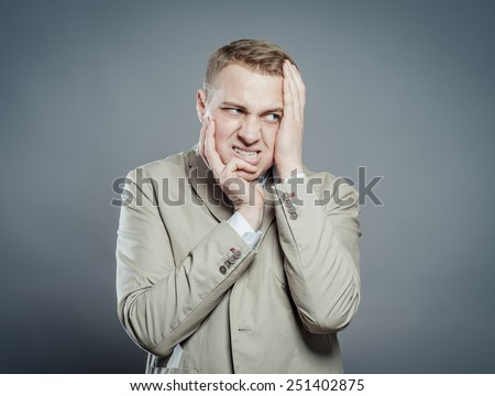 Expressions. Handsome young man in suit feeling fear with open mouth and closing eyes with hands - stock photo