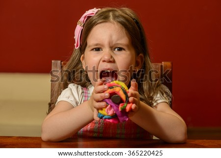 Expressive beautiful little girl playing indoor with colored pieces of clay, plasticine, being inventive