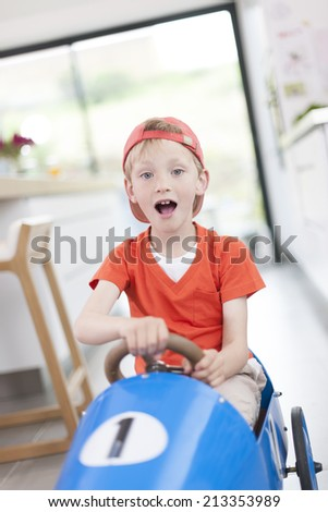 expressive boy playing with his pedal car at home - stock photo