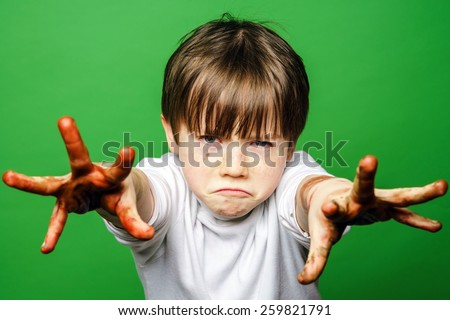 Expressive boy showing colorful hands after drawing, isolated on green - stock photo