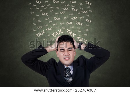 Expressive businessman in business suit thinks tax while holding his head
