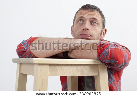 expressive casual man concept - lazy middle age man with checked shirt leaning on wooden stool expressing depression and frustration,white background - stock photo