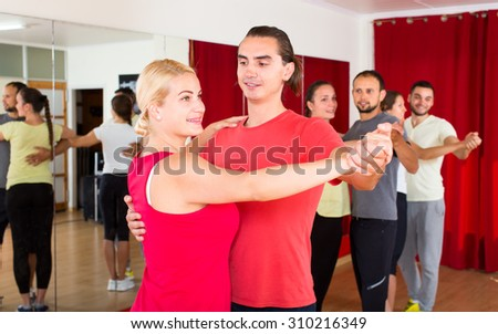Expressive couple learning to dance slow dances in a dancing studio with other people - stock photo