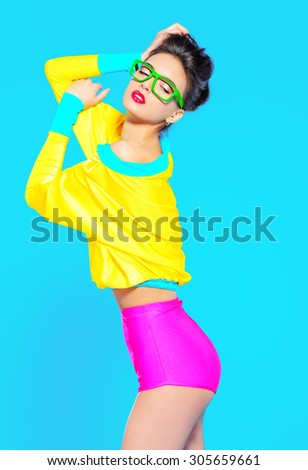 Expressive fashion model posing in vivid colourful clothes. Bright fashion. Optics, eyewear. Studio shot.