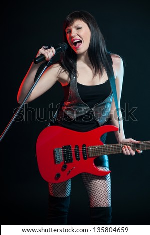 Expressive female rocker holding electric guitar and singing with mike, dark background - stock photo