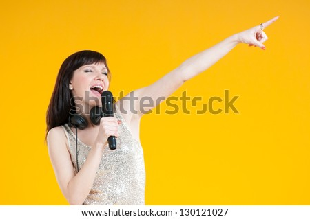 Expressive girl singing with a mike, yellow background
