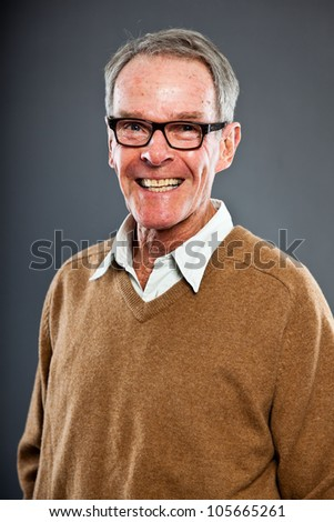 Expressive good looking senior man wearing glasses against grey wall. Funny and characteristic. Well dressed. Studio shot. - stock photo