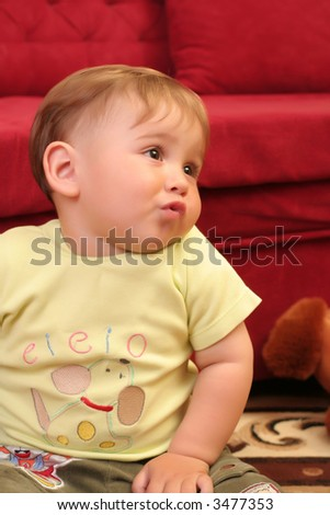 Expressive little blond baby boy gesticulate while playing with toys