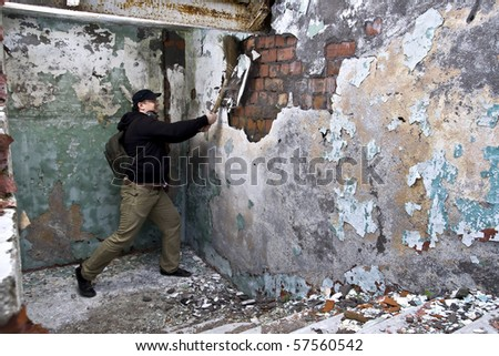 expressive man is damaging wall - stock photo