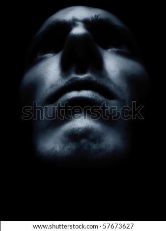 Expressive man portrait merging from the dark - stock photo