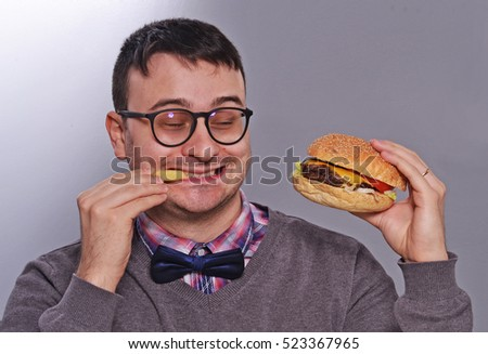 Expressive nerd eating burger and fried french potatoes.