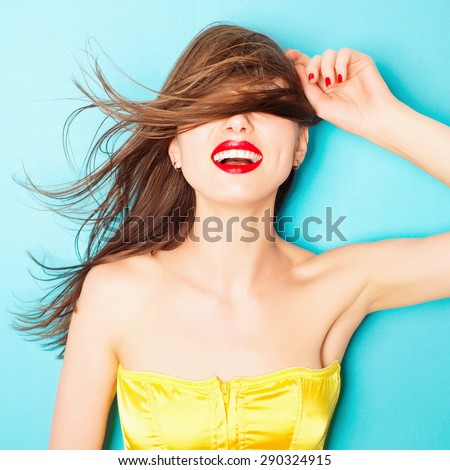 Expressive portrait of a beautiful brunette woman in the studio on a blue background, the concept of beauty - stock photo