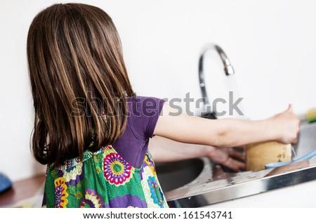 Expressive portrait of very cute girl doing crockery - stock photo