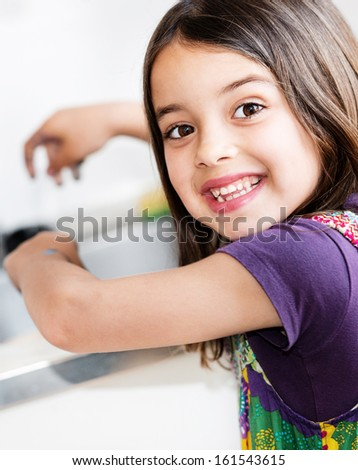 Expressive portrait of very cute girl washing hands