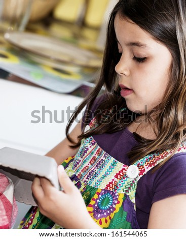 Expressive portrait of very cute girl wiping the dishes - stock photo