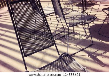 Expressive view at an assortment of chairs made of metal mesh, back lit by the afternoon sun coming in stripes, probably through a fence.