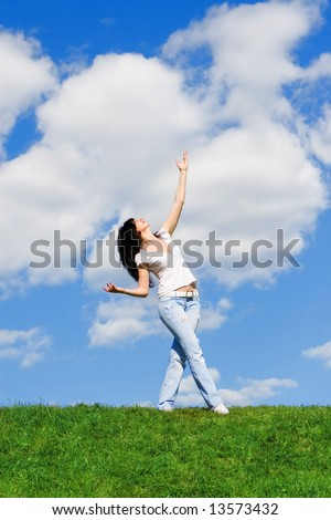 expressive woman dancing on green grass - stock photo