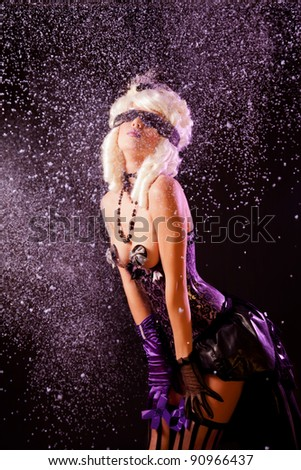 Expressive woman in burlesque outfit, with snow background - stock photo