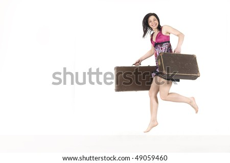 Expressive woman is jumping. She is holding suitcases.