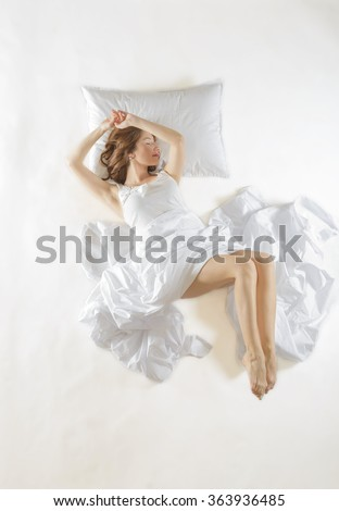 Expressive woman sleeping. Full length high angle view of a young woman sleeping on white background. Expressive woman in action, dreaming concept. - stock photo