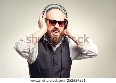 Expressive young bearded man in headphones standing against grey background listening to the music and sing - stock photo