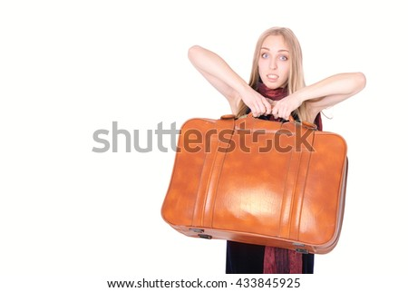 Expressive young woman carrying heavy suitcase, with copyspace (on white background) - stock photo