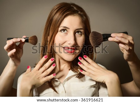 Expressive young woman feeling pretty, getting make-up applied by a makeup with two hands with brushes for makeup, studio shot on gray background. Makeup concept - stock photo
