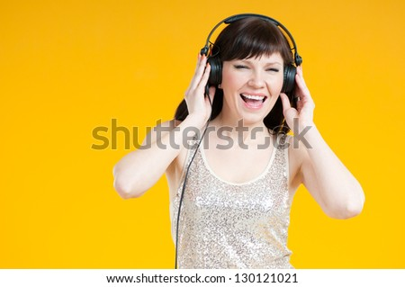 Expressive young woman listening to music in headphones - stock photo