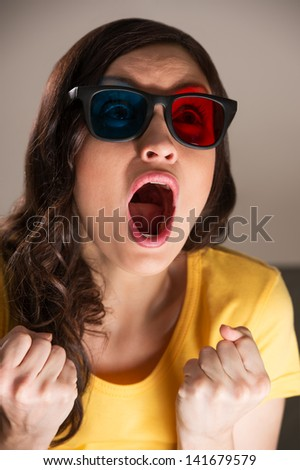 Expressive young woman watching 3d film in stereo glasses