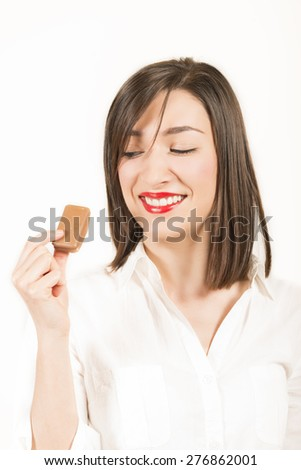 Expressive young woman with chocolate cookie in hand, looking at it, smiling, studio shot on white background - stock photo