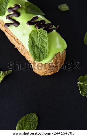 exquisite cream dessert eclair with fresh mint leaves - stock photo