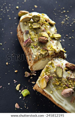 exquisite cream dessert eclair with pistachios with crumbs on the background - stock photo