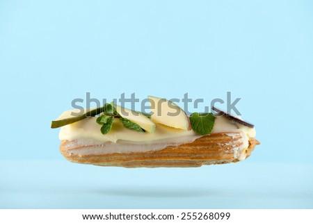 exquisite cream dessert eclair with slices of  fresh mango - stock photo