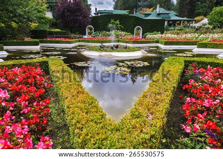 Exquisite fountain among the flower beds. Delightful landscaped and floral park Butchart Gardens on Vancouver Island - stock photo