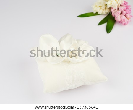 Exquisite pillow for wedding rings on gray background