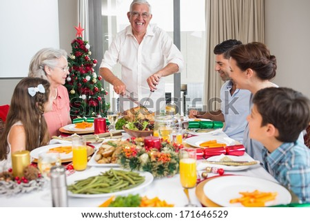 Extended family at dining table for christmas dinner in the house - stock photo
