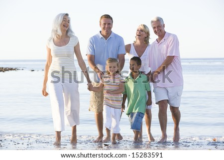 Extended family at the beach smiling - stock photo