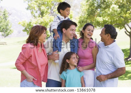 Extended family at the park smiling - stock photo