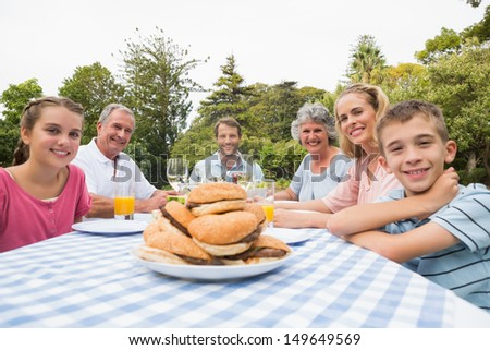 Extended family eating outdoors at picnic table smiling at camera - stock photo