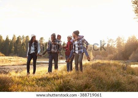 Extended Family Group Walking By Lake - stock photo